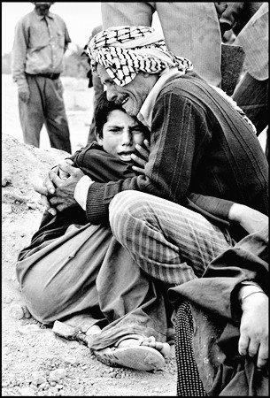 In Ahwaz cemetery, an uncle holds his nephew who lost his parents - 1981